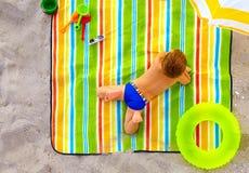 Nettes Kind, das auf buntem Strand ein Sonnenbad nimmt Lizenzfreies Stockfoto