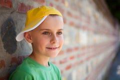 Nettes Kind, das auf einer Wand sich lehnt lizenzfreies stockbild