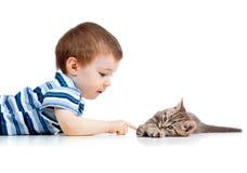 Nettes Kind, das auf Fußboden liegt und mit Katzehaustier spielt Lizenzfreie Stockbilder
