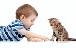 Nettes Kind, das auf Fußboden liegt und mit Katzehaustier spielt Lizenzfreies Stockbild