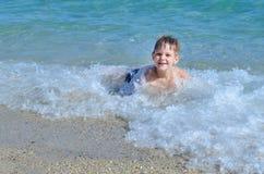 Nettes Kind, das in der Seewelle lächelt Stockbild