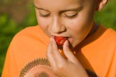Nettes Kind, das eine Erdbeere isst Lizenzfreie Stockfotos