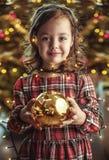 Nettes Kind, das eine Weihnachtsbaumglaskugel hält stockfotos