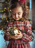 Nettes Kind, das eine Weihnachtsbaumglaskugel hält lizenzfreie stockfotos