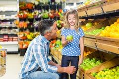 Nettes Kind, das einen grünen Apfel im Lebensmittelgeschäft hält stockfoto