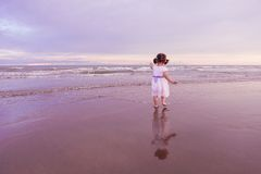 Nettes Kind, das entlang einen Strand auf Sonnenuntergang geht Stockfotografie