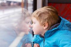 Nettes Kind, das heraus Zugfenster reist und draußen schaut Lizenzfreie Stockbilder