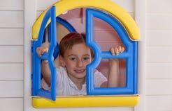 Nettes Kind, das im Spielzeughaus spielt Lizenzfreie Stockfotos
