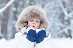 Nettes Kind, das mit Schnee in einem Winterpark spielt Lizenzfreies Stockbild