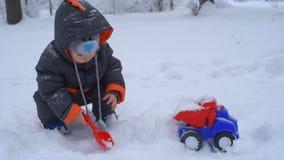 Nettes Kind, das mit Schnee spielt stock video