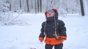 Nettes Kind, das mit Schnee spielt stock footage