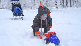 Nettes Kind, das mit Schnee spielt stock video footage