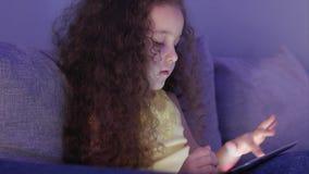 Nettes Kind, das mit Tablet unterhält Kleines Mädchen-Ausgaben-Freizeit, die bewegliches Spiel in und in den Zerstampfungen das h stock video