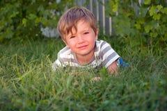 Nettes Kind, das Nebentätigkeiten hat Kind auf dem Gras lizenzfreie stockfotografie