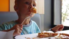 Nettes Kind, das Pizza mit Appetit im Schnellrestaurant isst Volle hd RealzeitVideoaufnahmen stock video