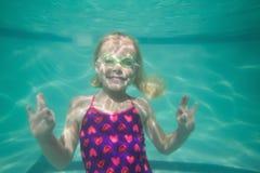 Nettes Kind, das unter Wasser im Pool aufwirft Lizenzfreies Stockfoto