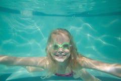 Nettes Kind, das unter Wasser im Pool aufwirft Stockbild