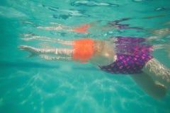 Nettes Kind, das unter Wasser im Pool aufwirft Stockfotos