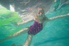 Nettes Kind, das unter Wasser im Pool aufwirft Lizenzfreie Stockfotos