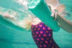 Nettes Kind, das unter Wasser im Pool aufwirft Stockbilder