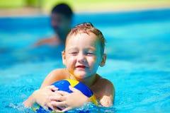 Nettes Kind, das Wassersportspiele im Pool spielt Lizenzfreie Stockbilder