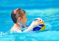 Nettes Kind, das Wassersportspiele im Pool spielt Stockfotografie