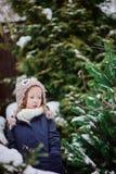 Nettes Kind in der Eulenstrickmütze auf dem Weg im schneebedeckten Garten des Winters Stockfoto