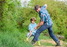 Nettes Kind in der Natur, die Spa? mit Cowboyvati hat Finden Sie Sch?tze Wenig Junge und Vater mit der Schaufel, die nach Sch?tze lizenzfreies stockbild