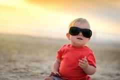 Nettes Kind in der Sonnenbrille, die auf Sand sitzt Lizenzfreies Stockfoto