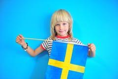 Nettes Kind des blonden Haares, das Flagge von Schweden hält lizenzfreies stockfoto