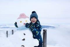 Nettes Kind, errichtender Schneemann und Spielen mit ihm auf Berg Stockfotos
