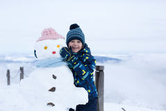 Nettes Kind, errichtender Schneemann und Spielen mit ihm auf Berg Stockfoto