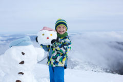 Nettes Kind, errichtender Schneemann und Spielen mit ihm auf Berg Lizenzfreie Stockfotos