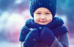 Nettes Kind in gestrickter Abnutzung und felted Mantel unter Winterschnee stockbild
