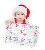 Nettes Kind im Sankt-Hut, der im Geschenkkasten sitzt Lizenzfreie Stockbilder