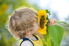 Nettes Kind mit Sonnenblume auf sonnig-grünem backgroun Lizenzfreies Stockfoto