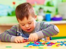 Nettes Kind mit unten ` s Syndrom, das im Kindergarten spielt lizenzfreie stockfotografie
