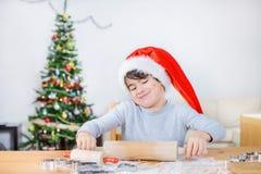 Nettes Kind rollt Teig mit Weihnachtsbaum hinten Lizenzfreie Stockfotos