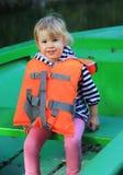 Nettes Kind sitzen im Boot mit Schwimmweste Lizenzfreie Stockfotos