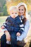 Nettes Kind und hübsche Mamma draußen am Fall. Stockbilder