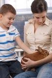 Nettes Kind und Mama mit Haustierhäschen Stockbild