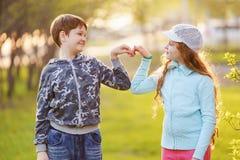 Nettes Kinderhändchenhalten in einer Herzform im Frühjahr draußen stockfotografie