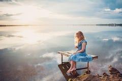 Nettes Kindermädchen, das auf einer hölzernen Plattform durch den See sitzt lizenzfreie stockfotos