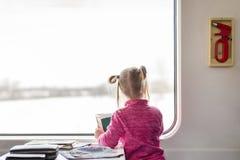Nettes Kindermädchen, das durch Eisenbahn reist Kind, das im Zug lächelt und sitzt Baby, das im breiten hellen sonnigen Fenster s Stockbilder