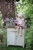 Nettes Kindermädchen, das im Frühjahr lila blühenden Garten des Kranzes macht Stockbild