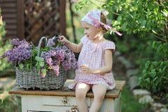 Nettes Kindermädchen, das im Frühjahr lila blühenden Garten des Kranzes macht Lizenzfreie Stockfotos