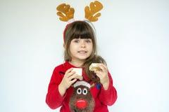 Nettes Kindermädchen, das Sankt-Hut trägt und frohe Feiertage wünscht stockbilder