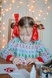 Nettes Kindermädchen, das Weihnachtspostkarten macht Stockbilder