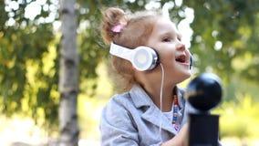 Nettes Kindermädchen in den Kopfhörern hörend Musik und ein Lied in einem Park mit Birken singend stock footage
