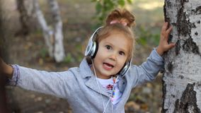 Nettes Kindermädchen in den Kopfhörern hörend Musik und ein Lied in einem Park mit Birken singend stock video footage